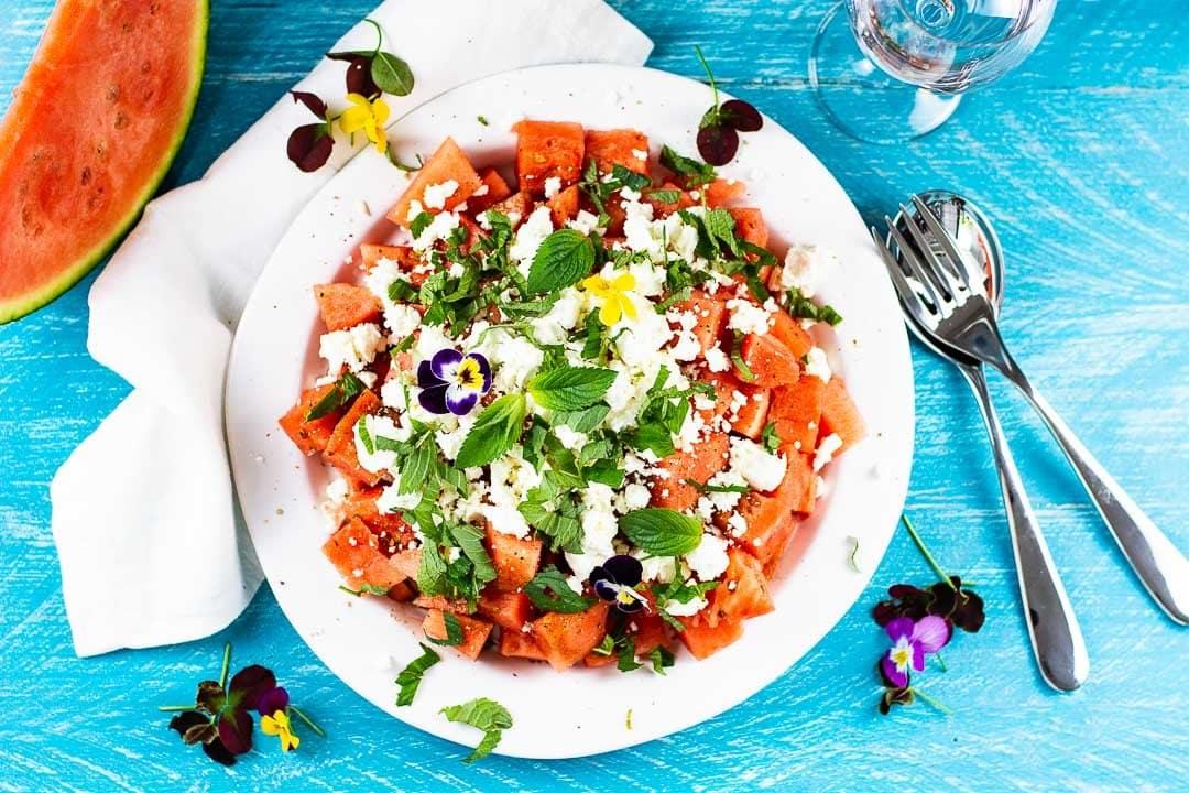 Wassermelonensalat mit Feta und Minze auf einem weißen Teller. An der Seite ist eine Wassermelone als Deko