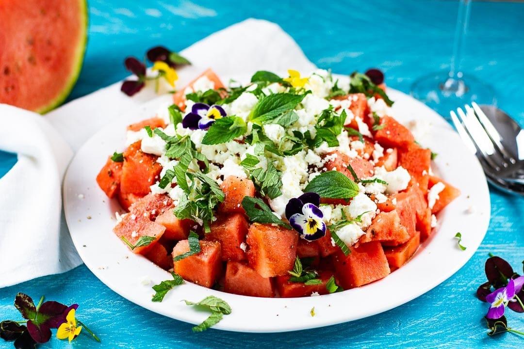 Ein Teller mit Wassermelonensalat, Feta und Minze. Daneben liegt Besteck
