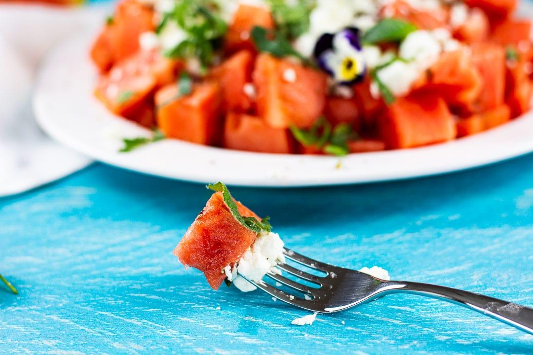 Eine Gabel mit einem Stück Wassermelone und einem Stück Feta Käse