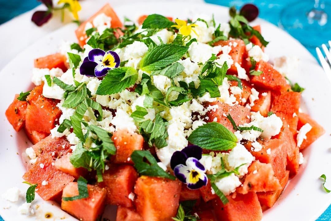 Ein Wassermelonensalat mit Minze, Feta und einem Blüttenblatt als Deko