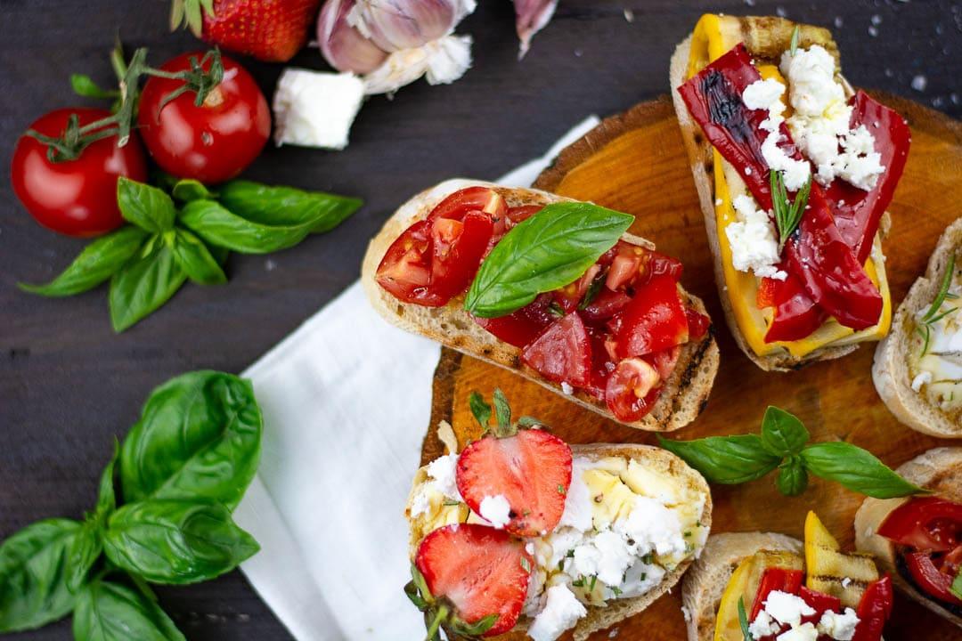 Ein Tisch mit dreierlei Bruschetta. Daneben liegen Tomaten, Basilikum und Erdbeeren