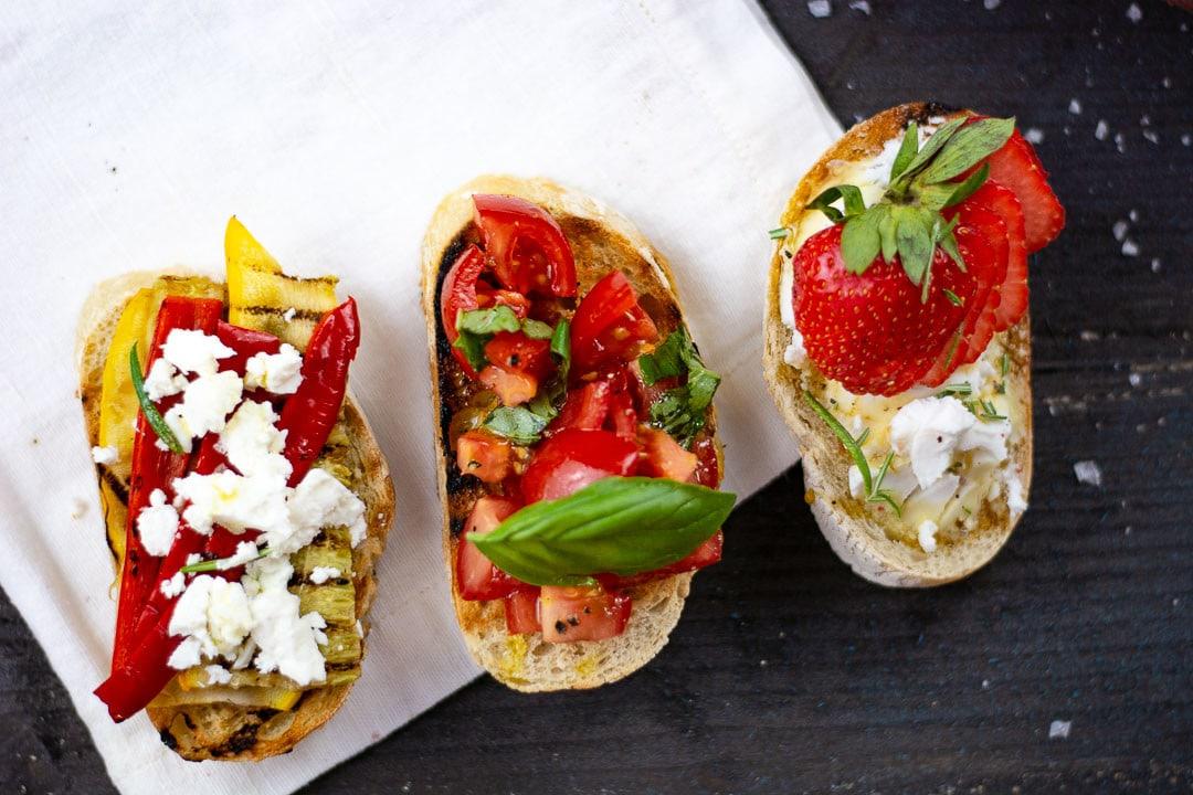 Drei Bruschetta von oben, belegt mit Gemüse, Frischäse und Erdbeeren