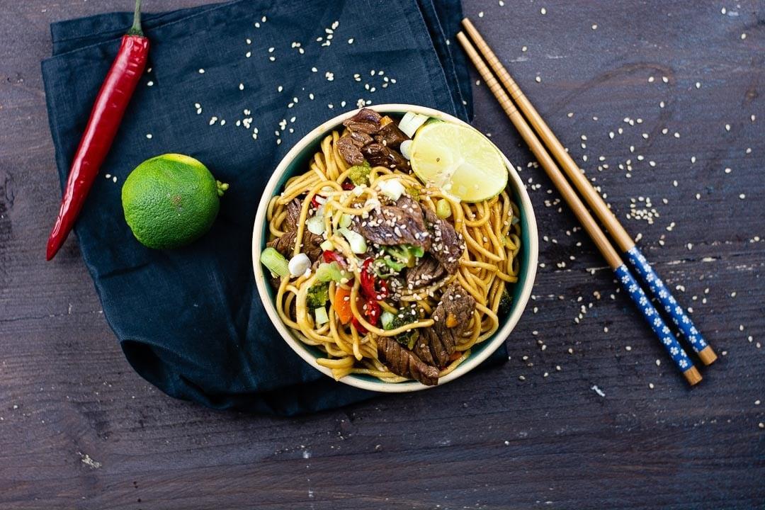 Ein Teller Asia Nudeln mit Rindfleisch und Gemüse. Daneben liegt eine Chili und eine Limette