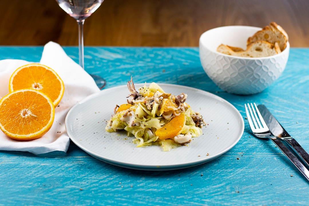 Ein Teller Calamari Salat mit einem Weinglas und Besteck