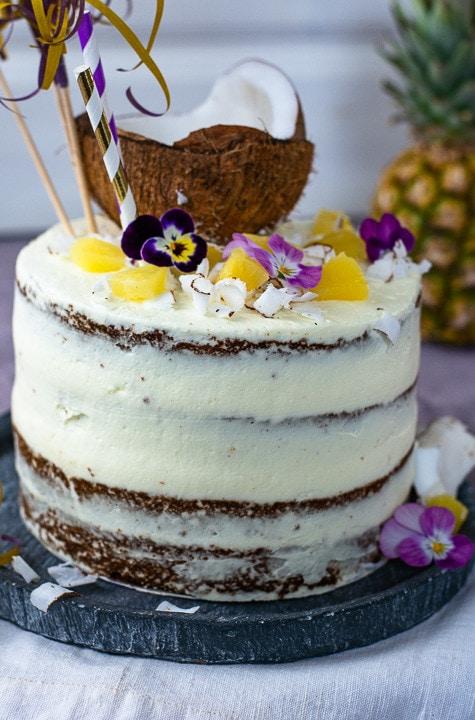 Eine ganze Pina Colada Torte auf einem Teller mit viel Dekoration