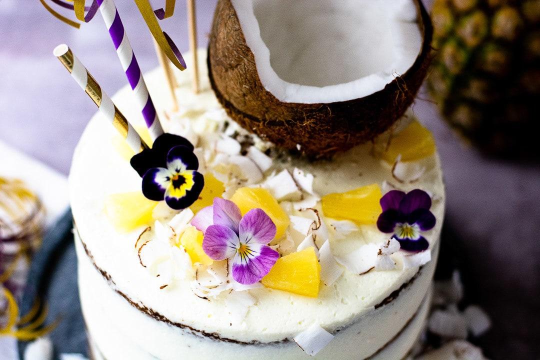 Die Pina Colada Torte gan nah. Man erkennt die weiße Creme und die dunklen Böden hervorschauen
