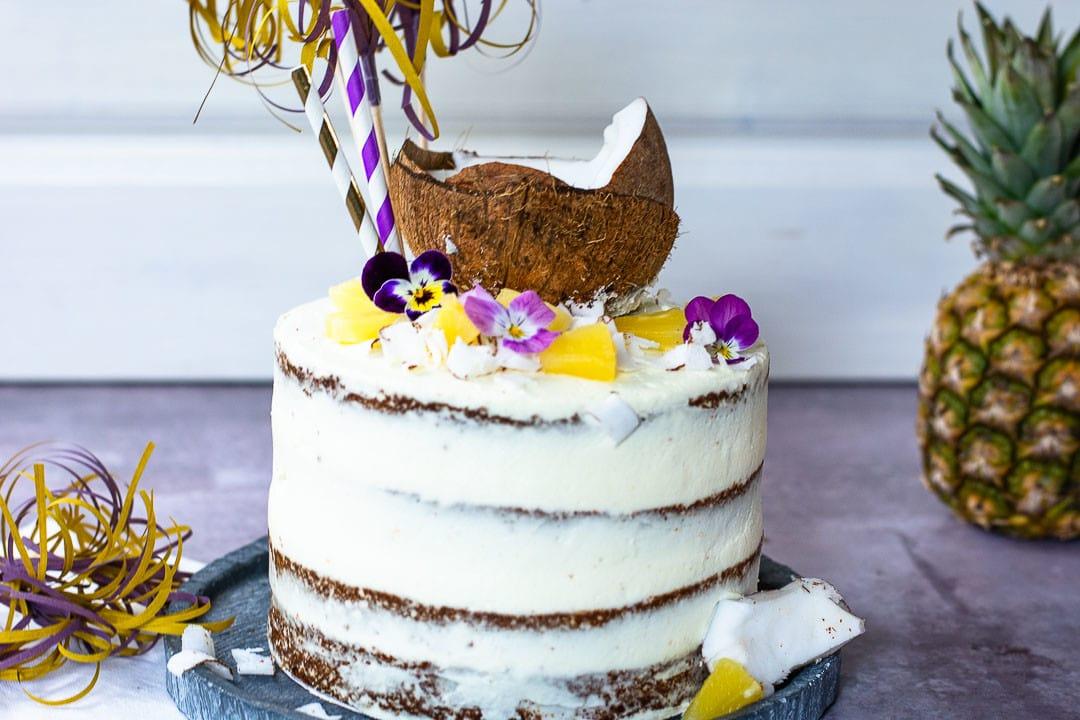 Eine Pina Colada Torte von der Seite. Es ist eine naked Cake Torte