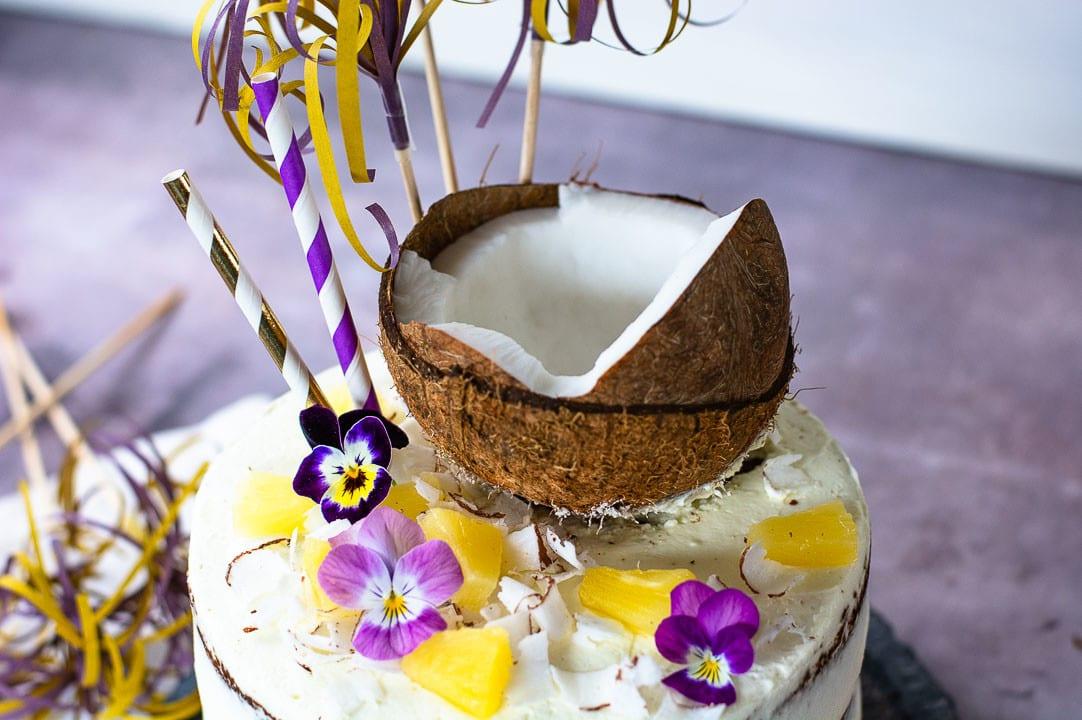 Die Pina Colada Torte von oben. Sie hat eine halbe Kokosnuss, Ananas und Blüttenblätter als Dekoration