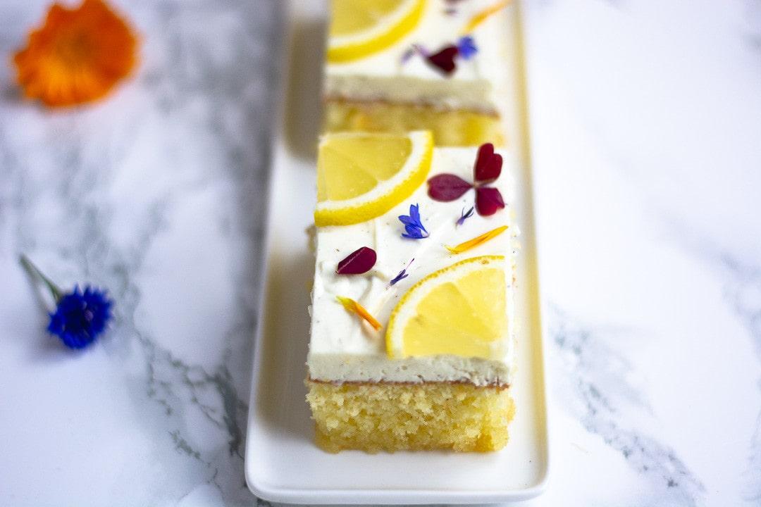 Ein Stück Zitronenkuchen mit Quark. Auf dem Zitronnekuchen, liegt eine Scheibe Zitrone und farbenfrohe Blüten zur Dekoration