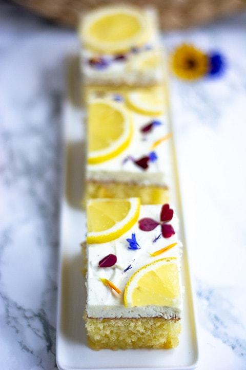 Drei Stücke Zitronenkuchen mit Quark. Im Hintergrund sieht man unscharf zwei Blütenblätter