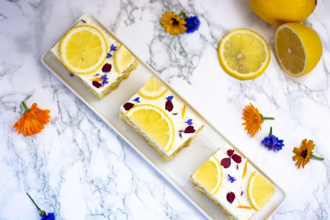 Drei Stücke Zitronenkuchen mit Quark auf einer länglichen Kuchenplatte