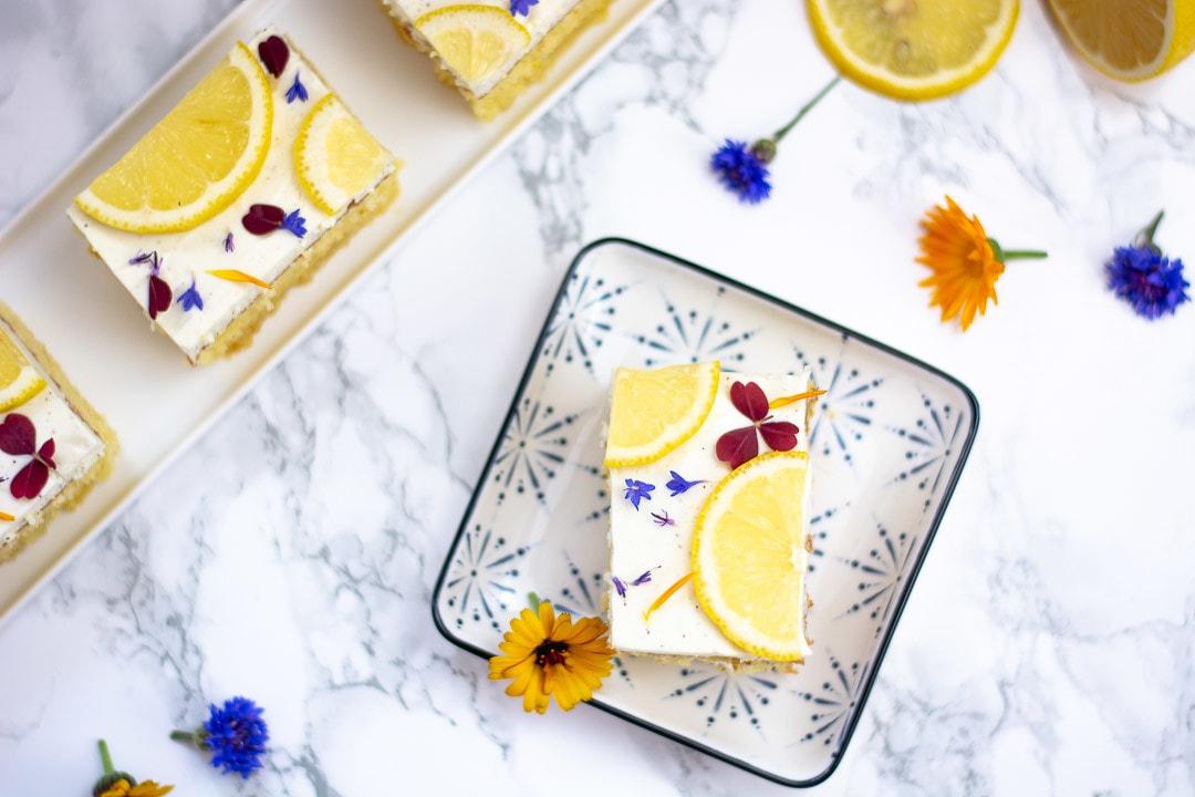 Ein Zitronenkuchen mit Quark auf einem quadratischen Teller