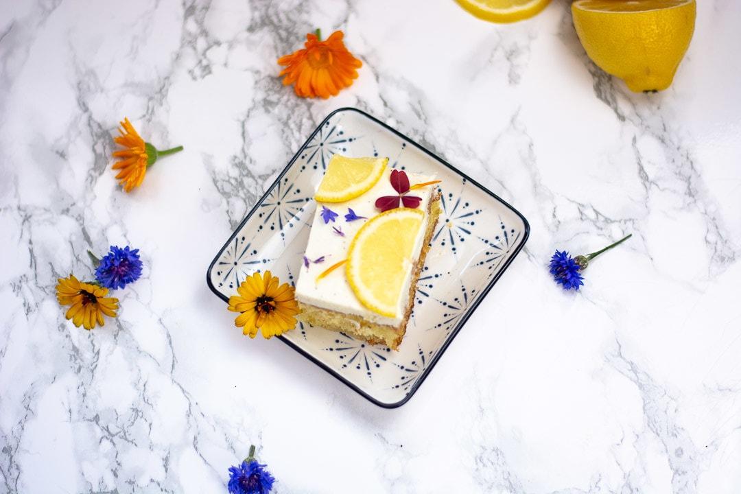 Ein Stück Zitronenkuchen mit Quark auf einem quadratischen Teller. Daneben liegen Blüten und eine halbe Zitrone