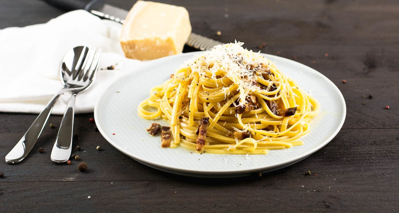 Spagetti Carbonara mit Parmesan bedeckt auf einem Teller. Im Hintergrund ist ein Stück Parmesan und eine Reibe