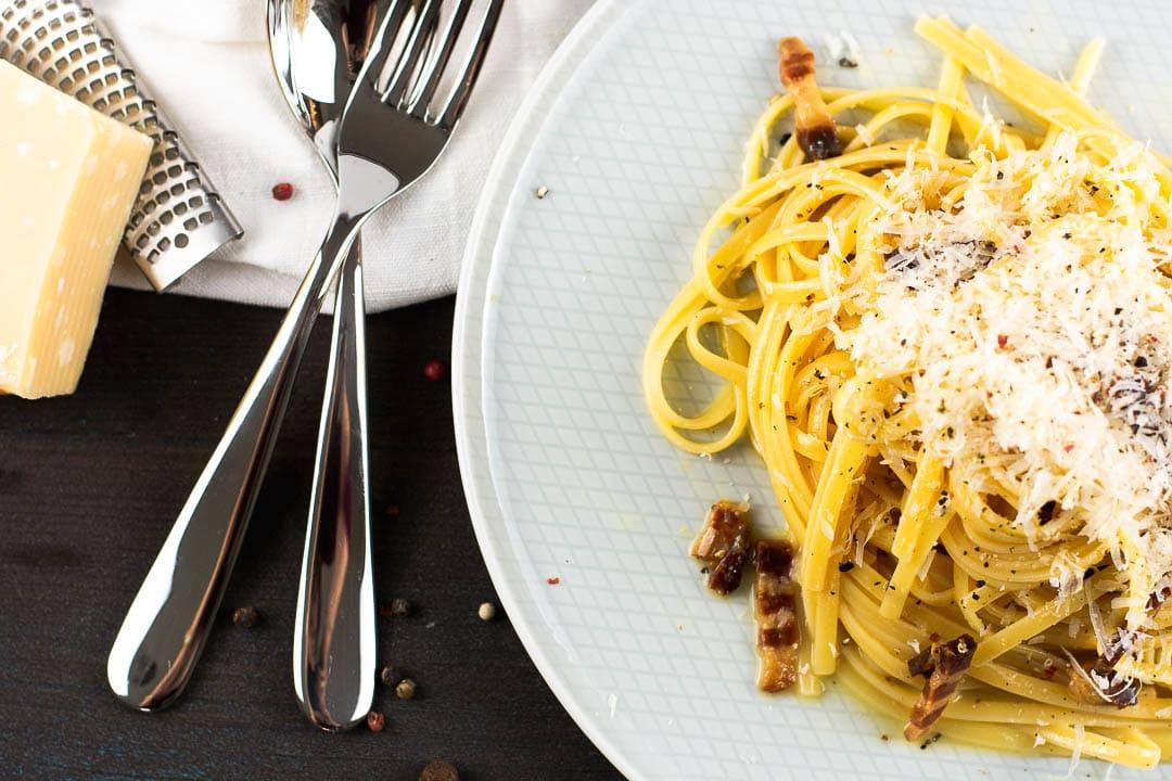 Ein Teller mit Spagetti Carbonara. Daneben liegt ein Löffel und eine Gabel