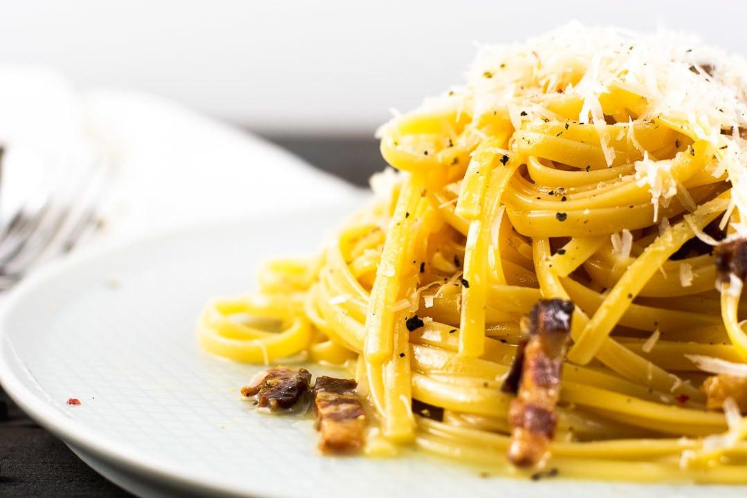 Eine Nahaufnahme der Spagetti Carbonara. Man sieht die Pfefferkörnchen und die Parmesansplitter auf der Carbonara