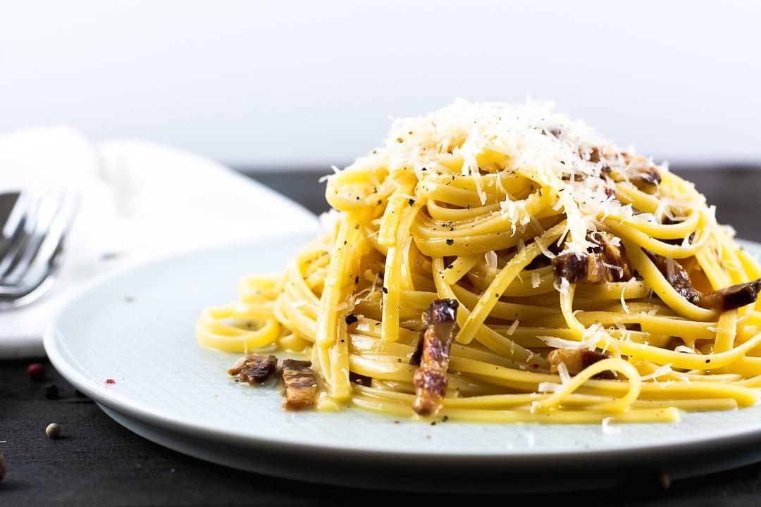 Spagetti Carbonara auf einem Teller. Oben drauf wurde Parmesan gerieben