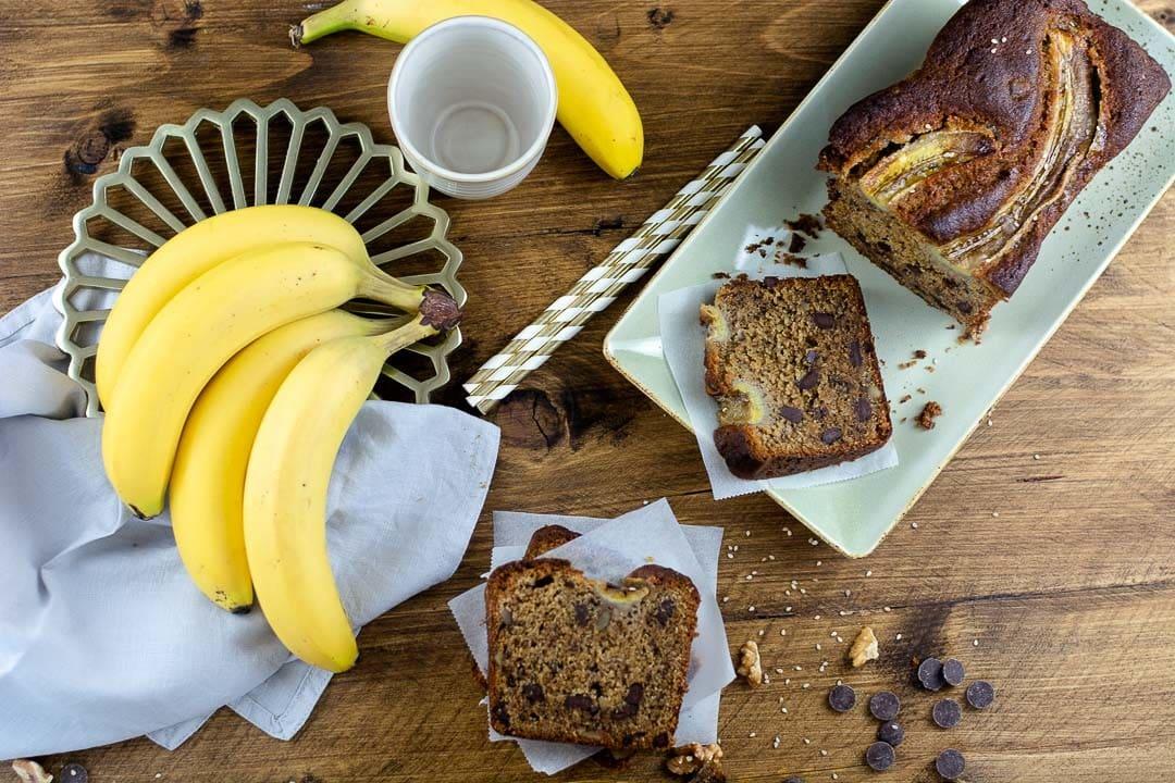 Ein angeschnittenes Bananenbrot, daneben liegen drei Stück des Bananenbrotes