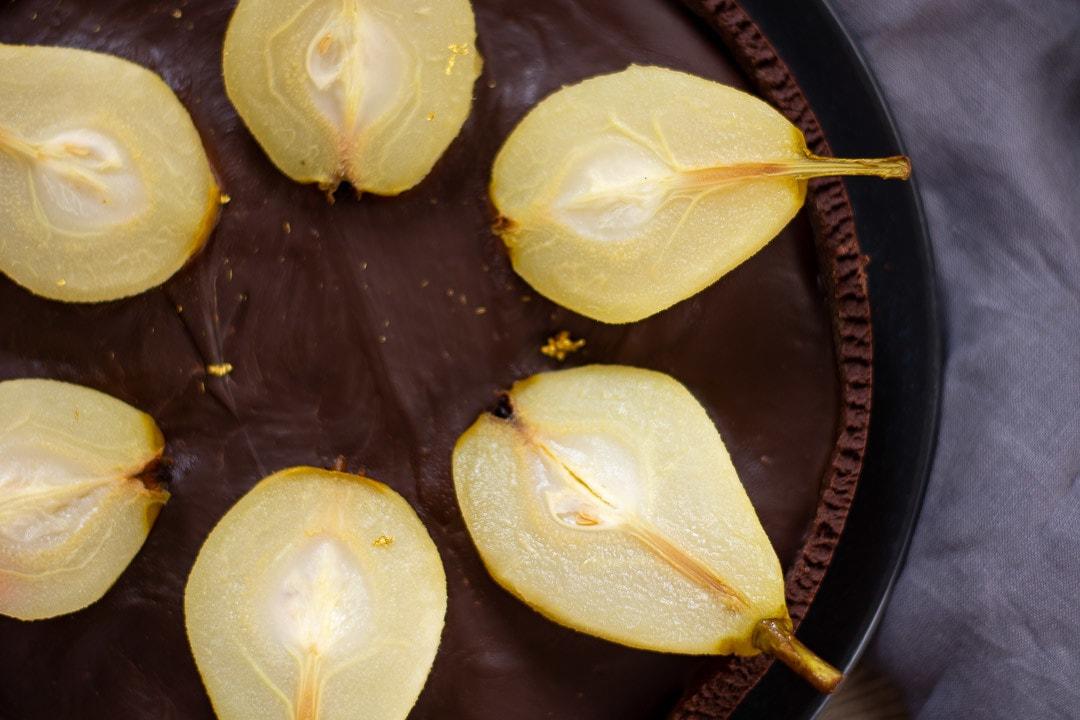 Eine Tarte mit viel Schokolade und Birnen auf einem schwarzen Teller
