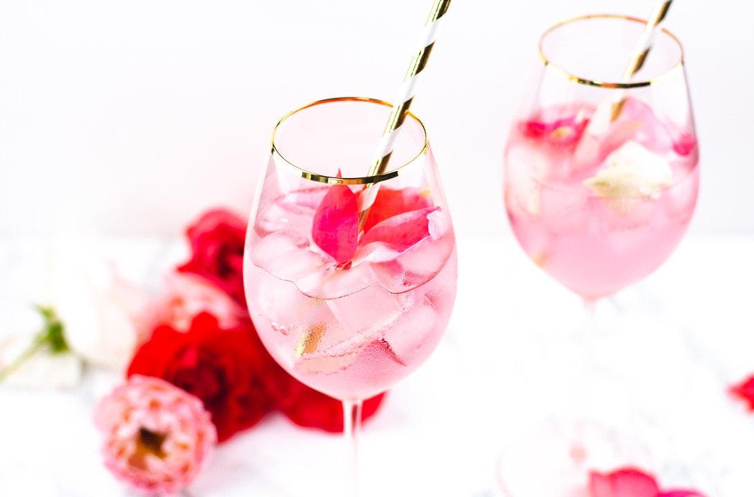 Ein Glas mit einem Rose Cocktail und einem goldenen Strohhalm