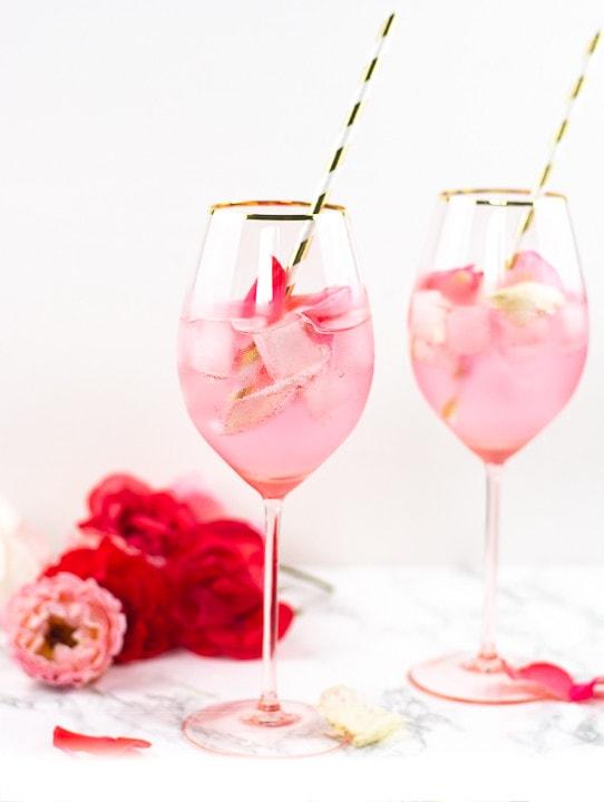 Zwei Gläser Rose Cocktail. Im Hintergrund liegen rote Rosen