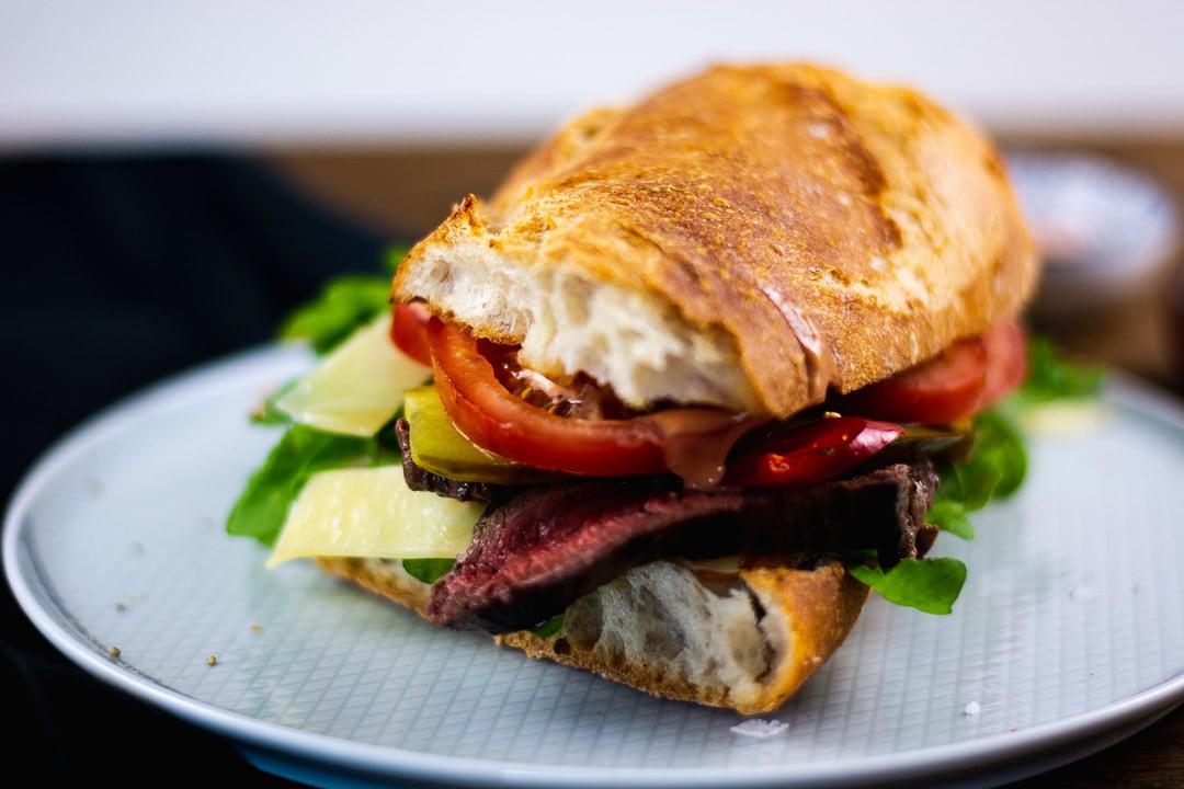 Das fertig Steak Sandwich auf einem hellblauen Teller
