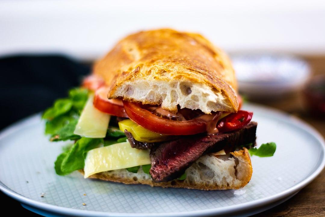 Ein Steak Sandwich aus dem vorne eine Tomate, ein Steak und Parmesan hervorschaut