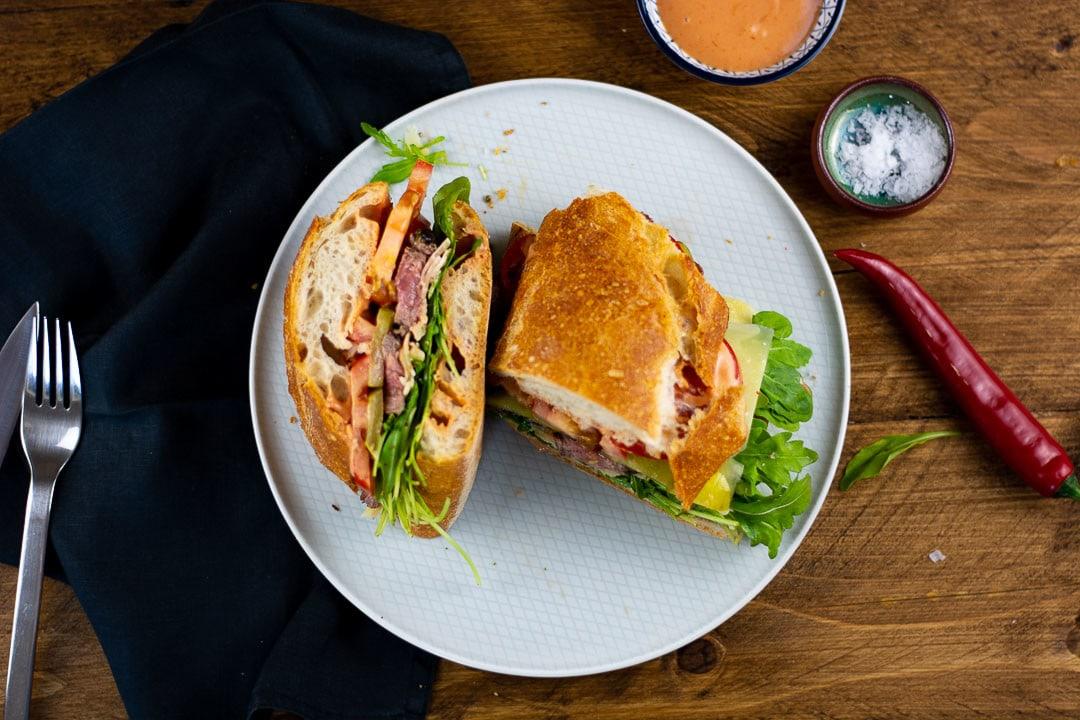 Das Steak Sandwich geteilt in zwei Stücke auf einem Teller. Daneben liegt eine rote Chili