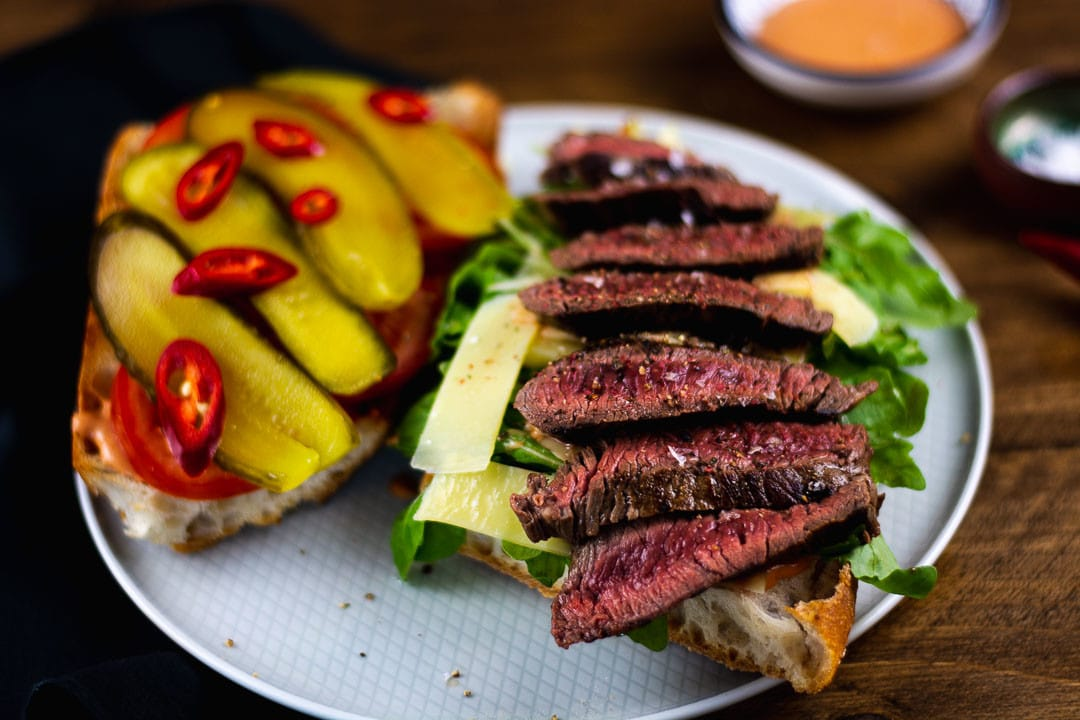 Ein Teller mit einem Steak Sandwich. Es ist aufgeklappt und man sieht das medium angebratenen Fleisch auf dem Sandwich liegen
