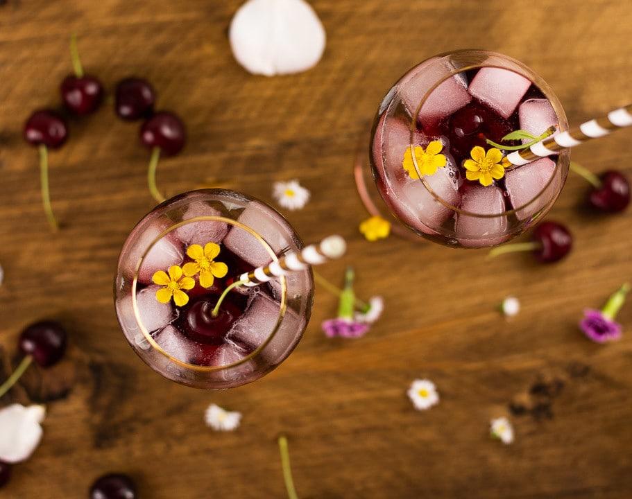 Zwei Cocktails mit Eiswürfel von oben. Man sieht Eiswürfel, eine Kirsche mit Stiehl und gelbe Blüttenblätter