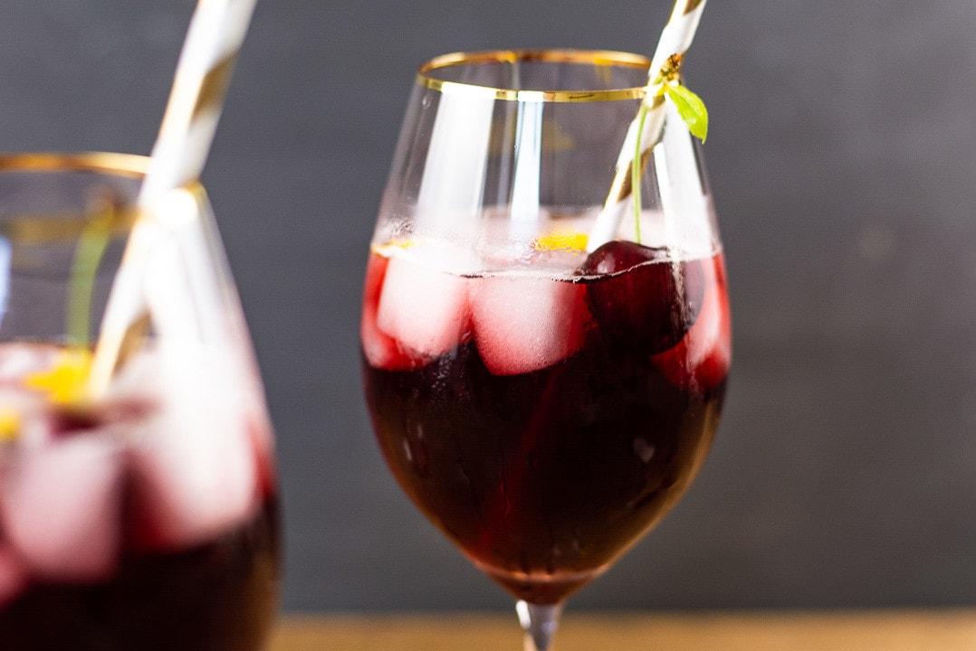 Ein Cocktail mit einer Kirsche und einem goldenen Strohhalm