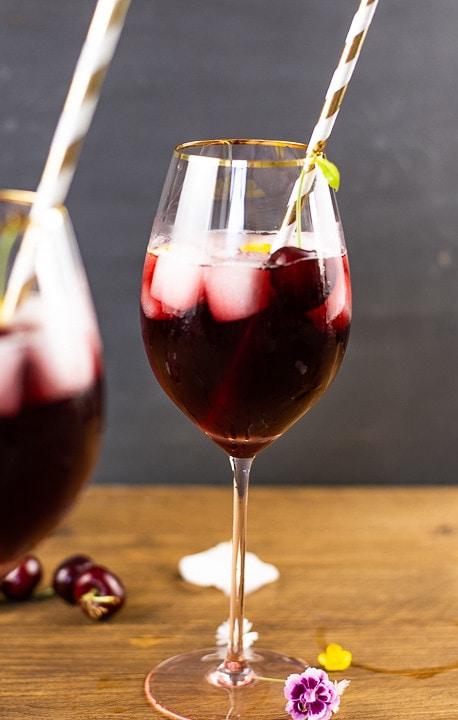Ein Weinglas gefüllt mit einem Kirschwasser Cocktail. Eine Kirsche mit Stiehl steht aus dem Glas hervor