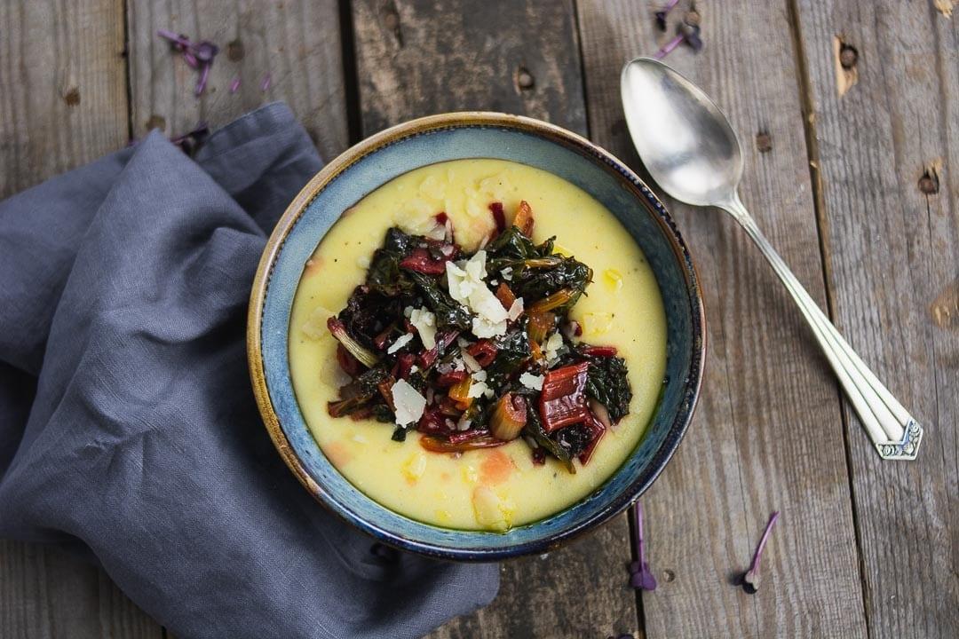 Ein Teller mit Polenta, man sieht Mangold auf der Polenta