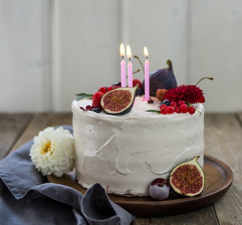 Eine Geburtstagstorte mit drei brennenden Kerzen und Feigen als Dekoration