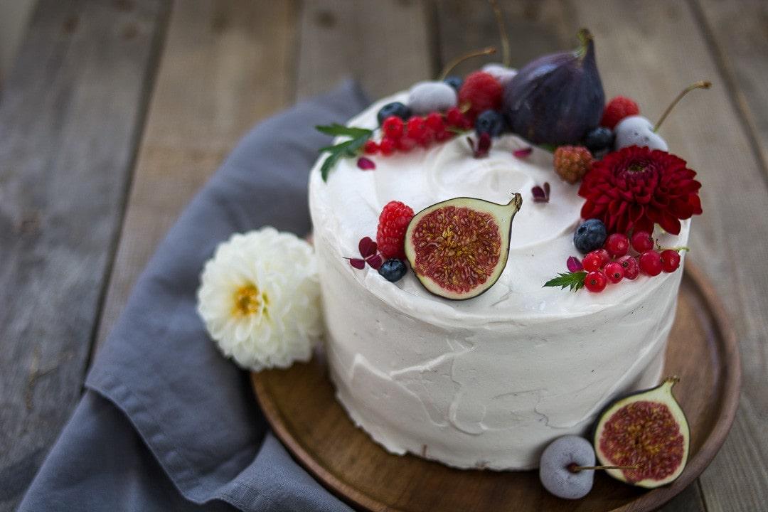 Eine weiße Geburtstagstorte mit fruchtiger Dekoration und echten Blumen