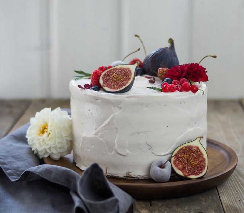 Auf einem Holzteller steht eine Torte. Sie ist weiß und ist mit Früchten dekoriert