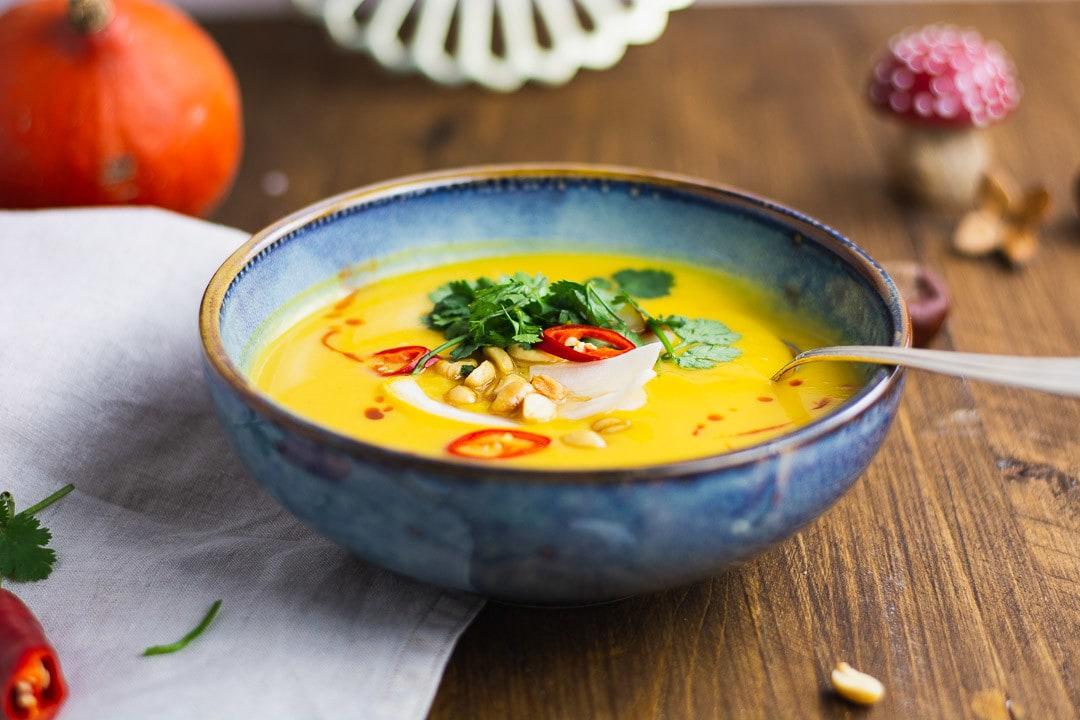 Ein Teller Kürbissuppe mit Erdnussbutter und ein Löffel schaut aus dem Teller hervor
