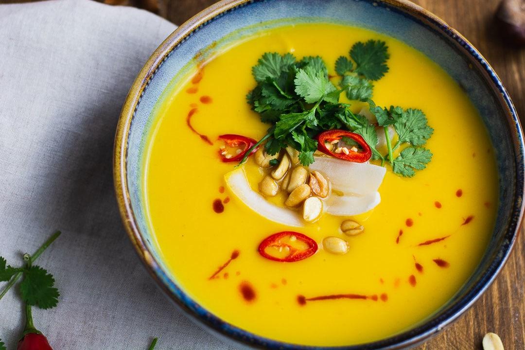 Die Kürbissuppe ganz nah. Man sieht Erdnüsse, Chili und Petersilie auf der Suppe