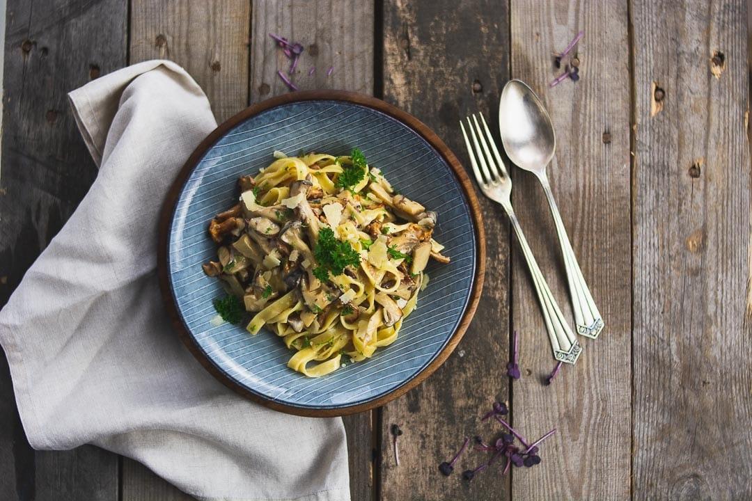 Waldpilze Pasta auf einem blauen Teller. Daneben liegen Messer und Gabel und eine Serviette