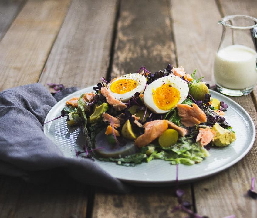 Der leckere Salat mit Sauce auf einem Holztisch