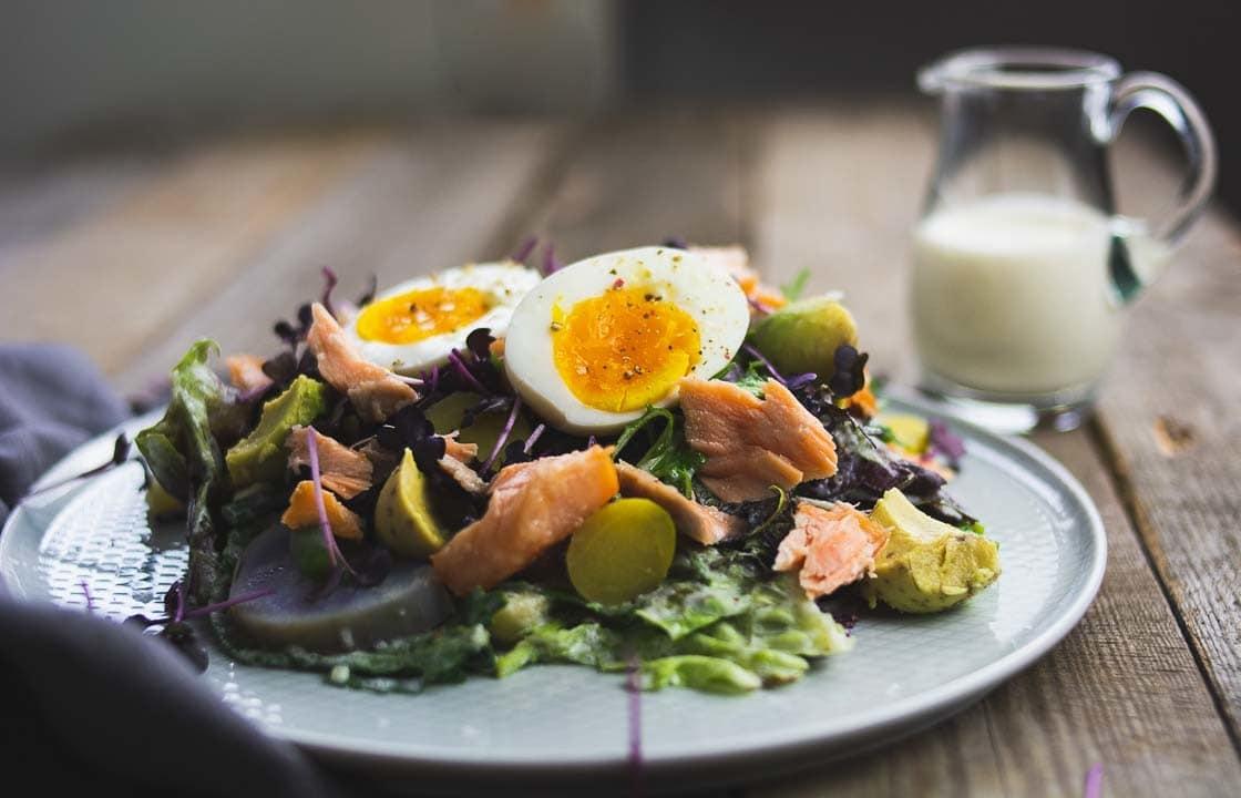 Zwei Eihälften liegen auf einem Salat