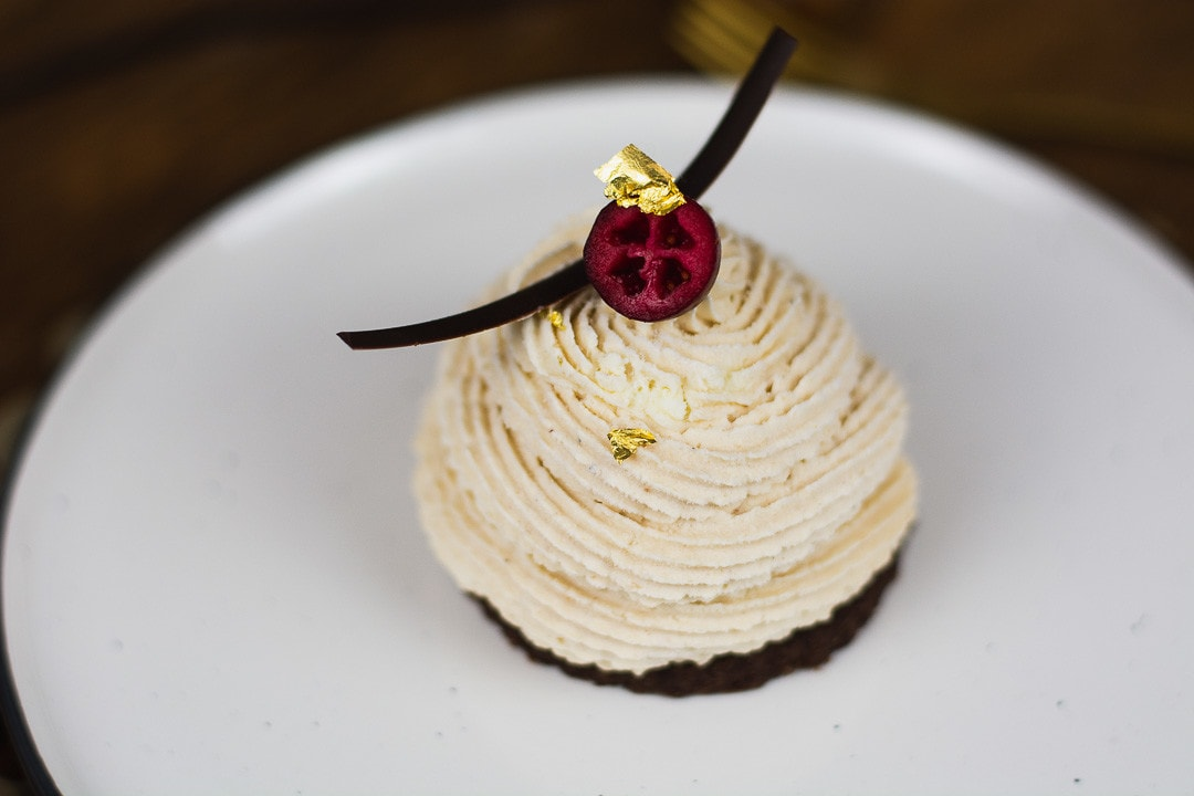 Nahaufname des Maronenmousse Törtchen. Es liegt eine Schokoladenspalte, eine Cranberry und ein Blatt Gold oben auf