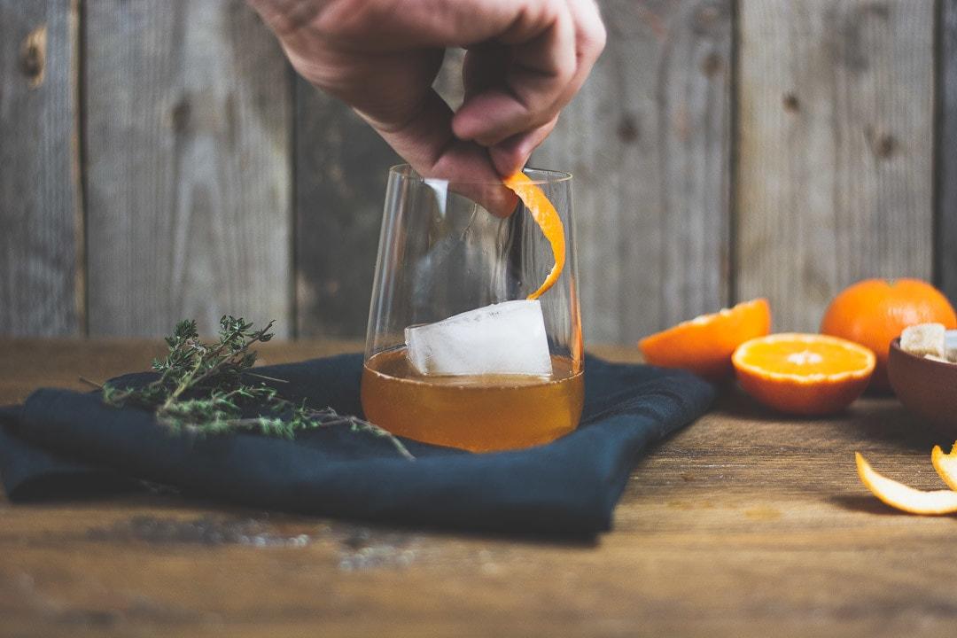 Eine Orangenzeste wird dem Old Fashioned hinzugegeben