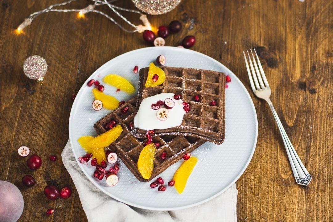 Ein Teller mit zwei Schoko Waffeln. Als Dekoration sind Cranberrys und Orangenscheiben auf den Waffeln
