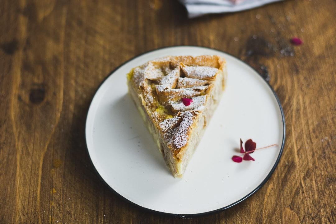 Ein Stück Filo Kuchen auf einem Teller mit einem Blütenblatt als Dekoration