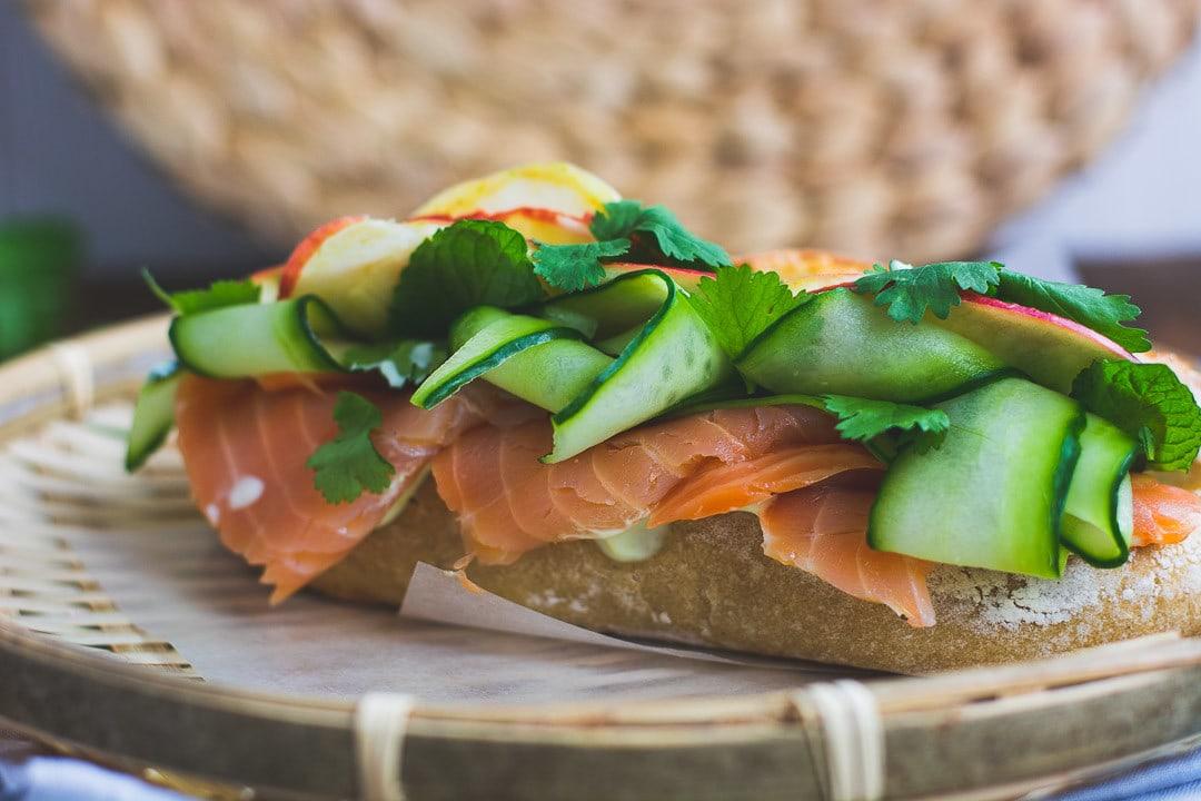 Lachs und Gurkenscheiben stehen aus einem Sandwich hervor