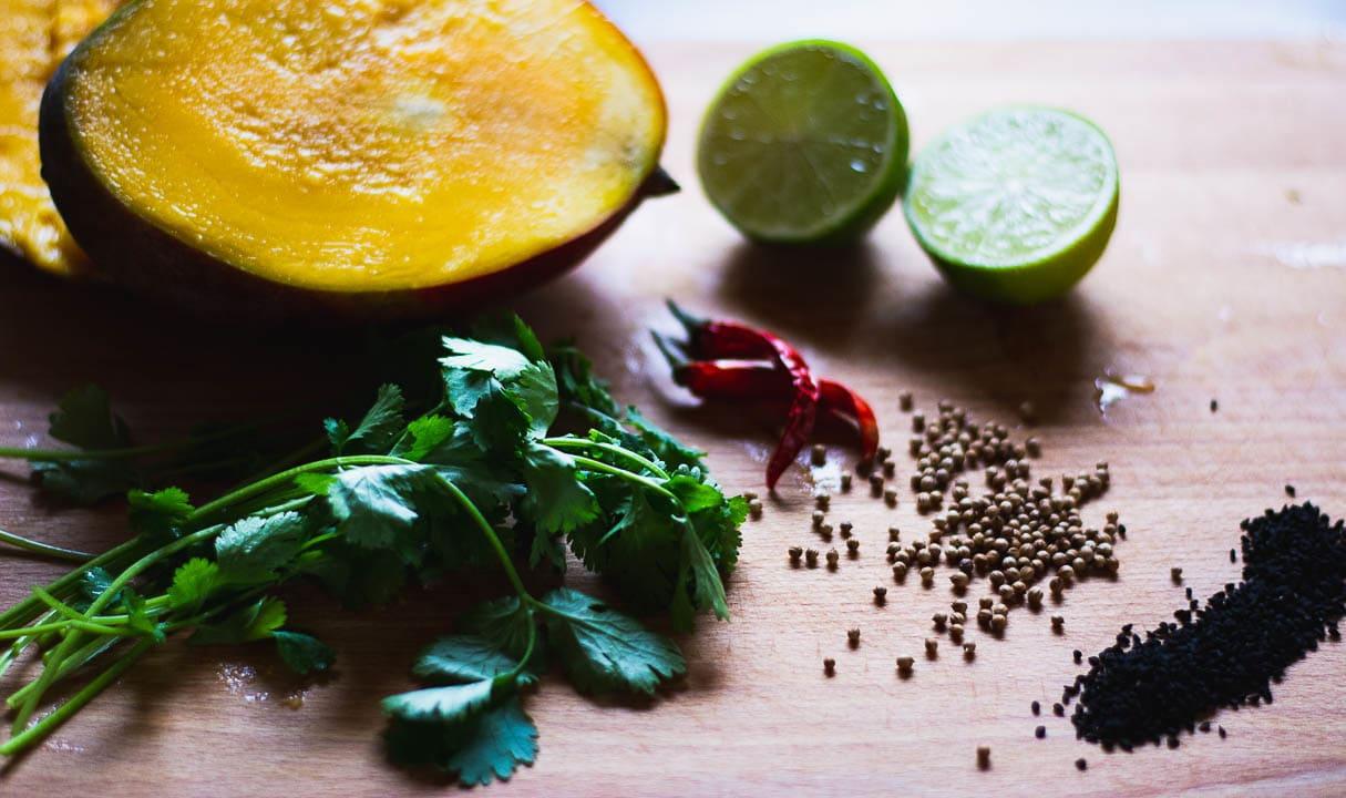 Eine Mango, Limetten, Chili und weiter Zutaten auf einem Tisch
