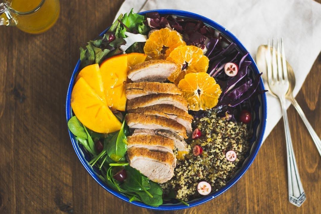 Salat auf dem eine Entenbrust zu sehen ist. Daneben liegt Besteck