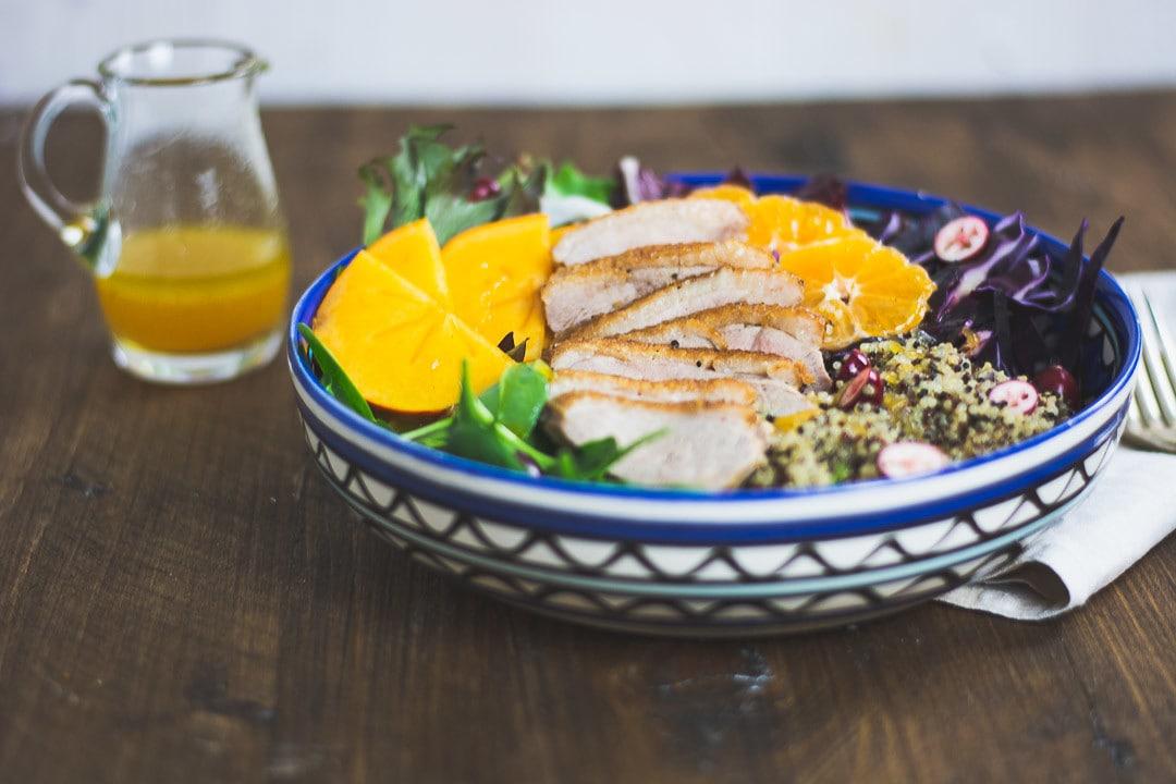 Ein Salat mit Entenbrust und einer Sauce daneben
