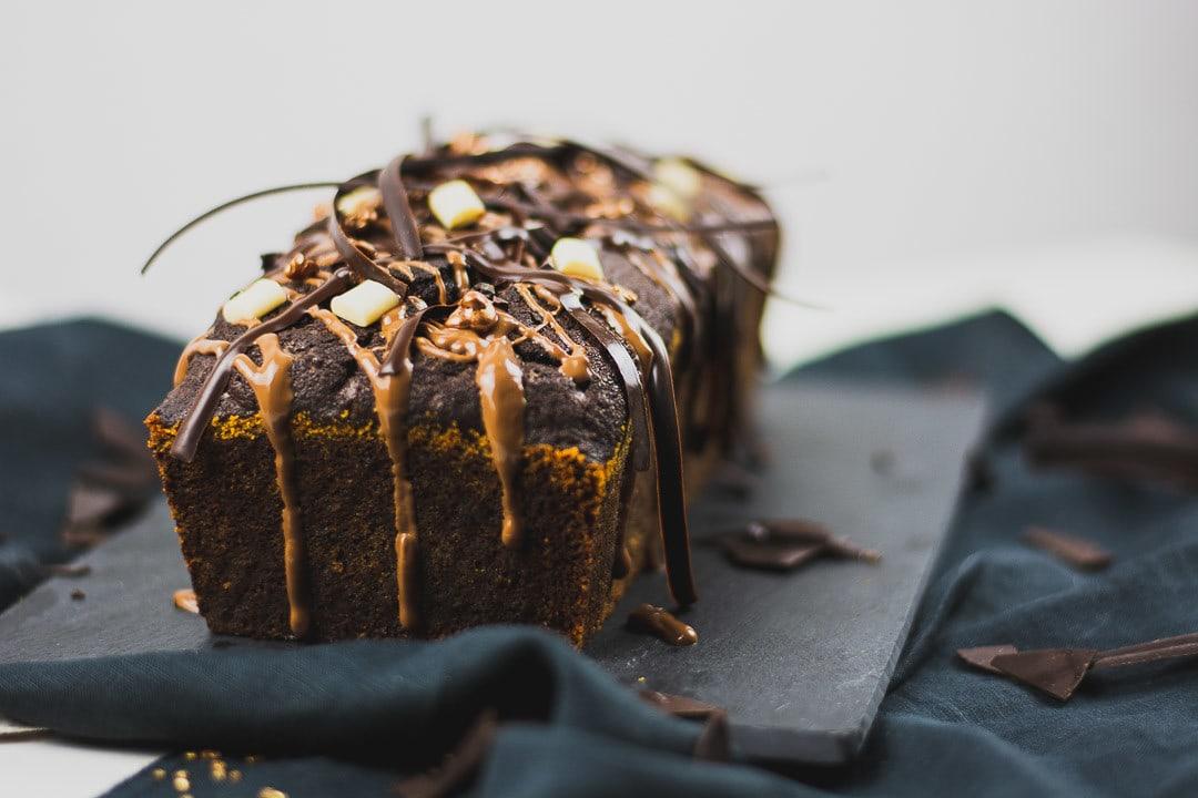 Der bester Schokokuchen, mit Karamell, weißen Schokoladenstückchen und Schokoladenstreifen dekoriert